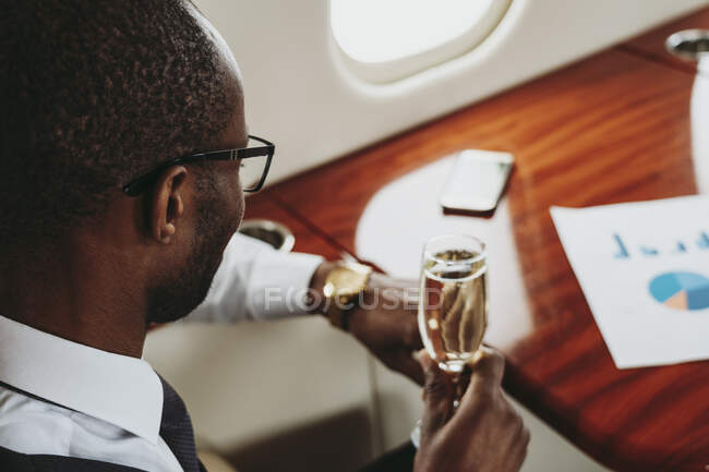 Young businessman with champagne traveling in airplane — Stock Photo