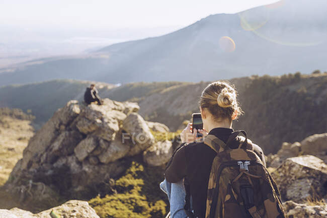 Young woman photographing male friend sitting on top of mountain — Stock Photo