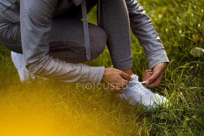 Спортсменка завязывала шнурки, приседая в парке — стоковое фото