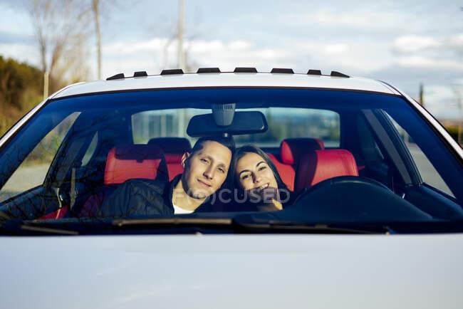 Молоде подружжя посміхається, сидячи в машині. — стокове фото