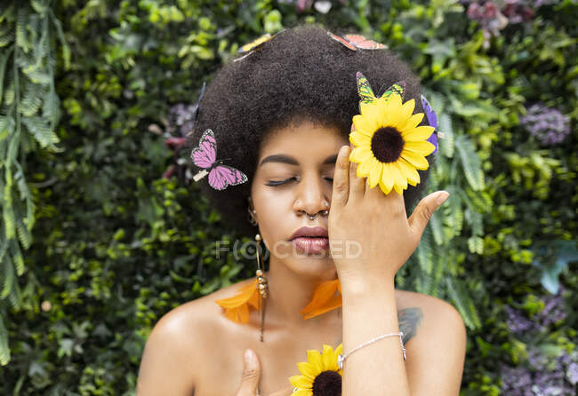 Афроженщина закрывает глаза рукой на растение — стоковое фото