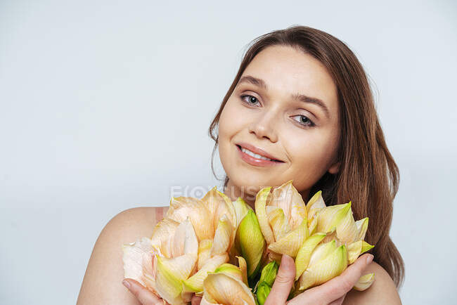 Young woman with flowers smiling while standing against white background — Stock Photo