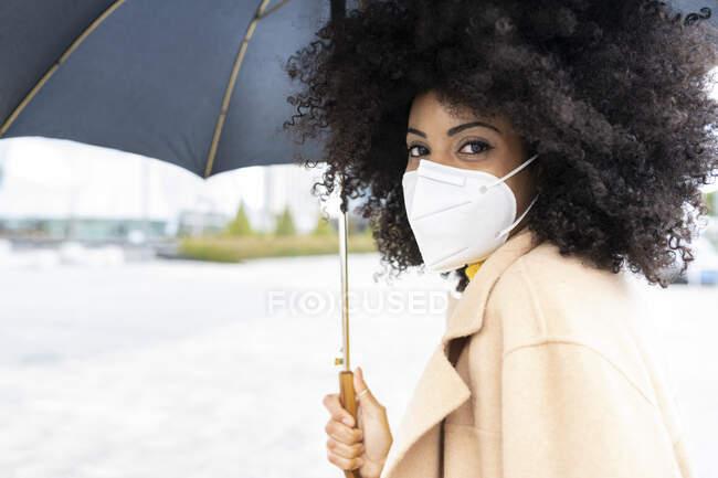 Mujer con máscara facial sosteniendo paraguas mientras está de pie al aire libre — Stock Photo