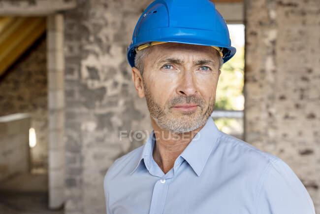 Arquiteto confiante vestindo chapéu duro olhando enquanto estava em pé no local de construção — Fotografia de Stock