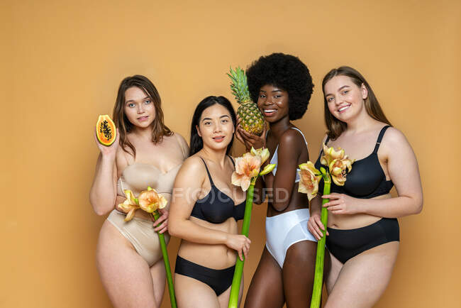 Multi-ethnic group of female models in lingerie holding artificial flowers and fruits against yellow background — Stock Photo