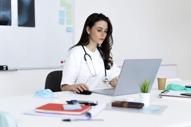 Consultoría médica en línea a través de laptop en clínica - foto de stock
