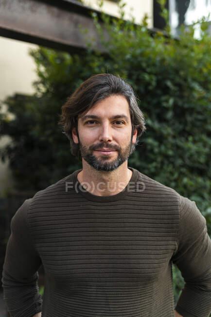 Портрет чоловіка у коричневому светрі, що стоїть надворі. — стокове фото