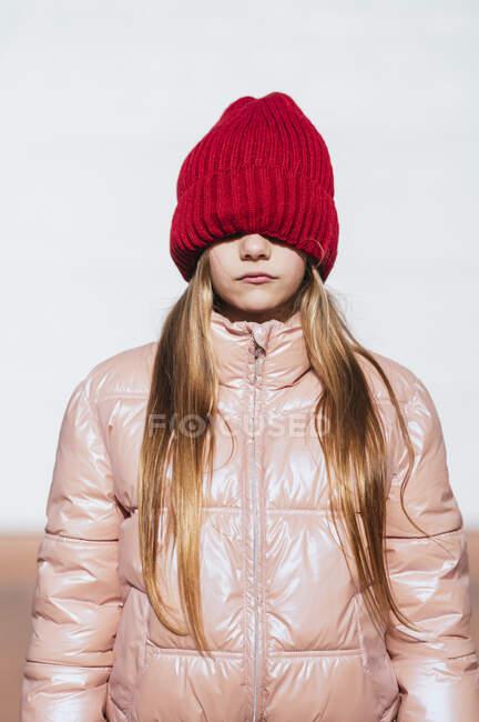 Девушка в настенной одежде закрывает глаза через вязаную шляпу к белой стене — стоковое фото