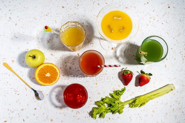 Multi colorido copos de coquetel de frutas saudáveis mantidos em mármore moderno terrazzo — Fotografia de Stock