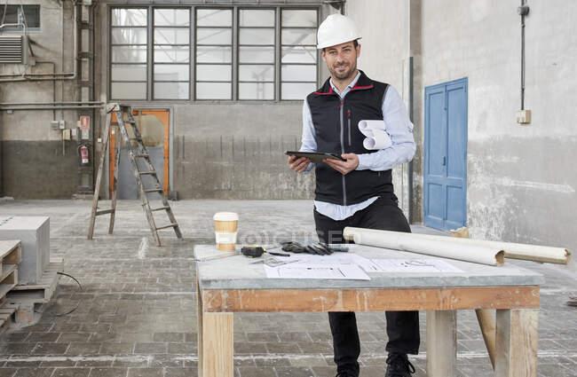 Architecte souriant avec tablette numérique debout à côté de la table sur le chantier — Photo de stock