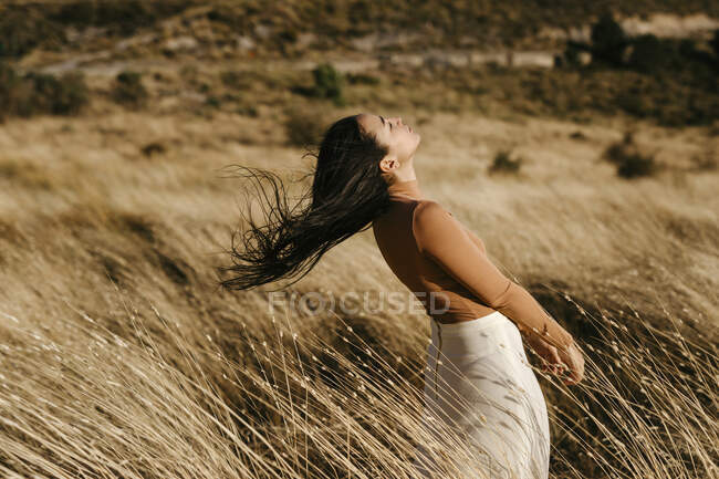 Carefree woman standing amidst grass in field during windy day — Stock Photo