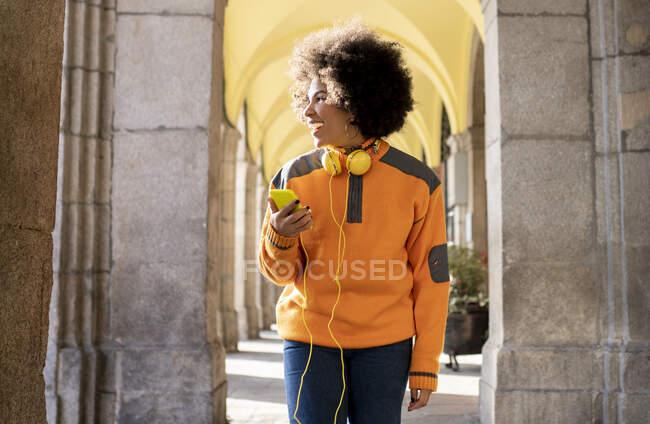 Mulher alegre com telefone celular e fones de ouvido olhando para longe enquanto caminhava no corredor — Fotografia de Stock
