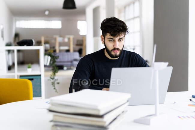 Молодий бізнесмен у творчому кабінеті користується ноутбуком. — стокове фото