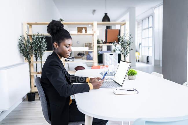 Junge Afro-Profi mit Smartphone, während sie mit Laptop am Schreibtisch im Büro sitzt — Stockfoto