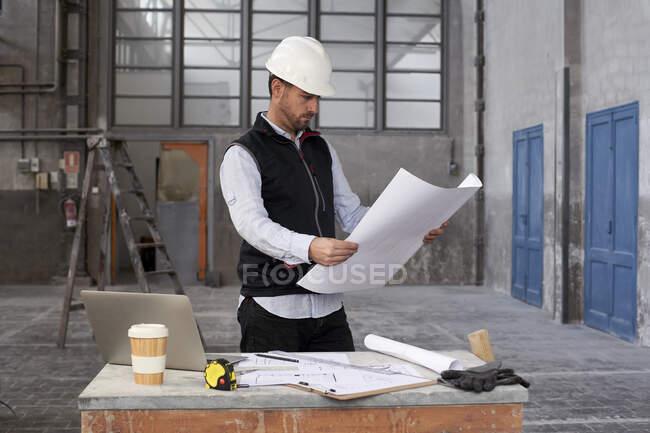Architecte masculin analysant le plan tout en se tenant à table dans le bâtiment — Photo de stock