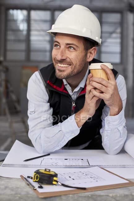 Architecte masculin souriant tenant le café en regardant loin tout en se tenant à table — Photo de stock