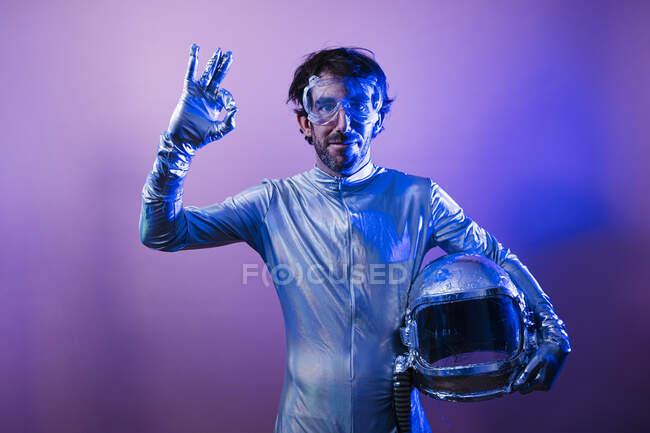 Astronauta macho sosteniendo casco espacial mientras muestra señal OK contra fondo de color - foto de stock