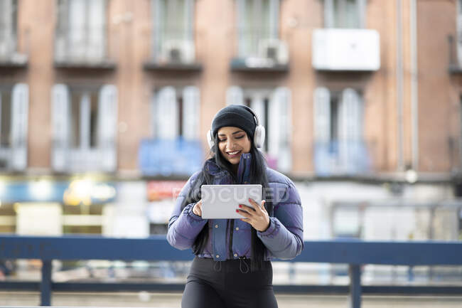 Mujer joven sonriente usando tableta digital mientras escucha música contra edificios en la ciudad - foto de stock