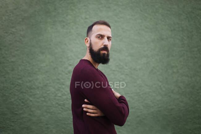 Barbudo hombre adulto medio con los brazos cruzados de pie por la pared verde - foto de stock