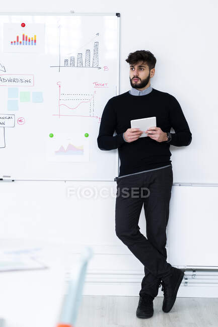 Businessman with digital tablet standing in front of whiteboard in office — Stock Photo