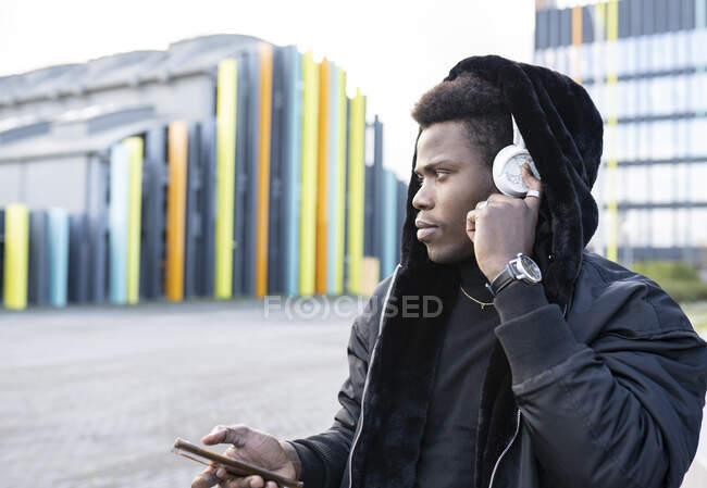Young man listening to music in city — Stock Photo