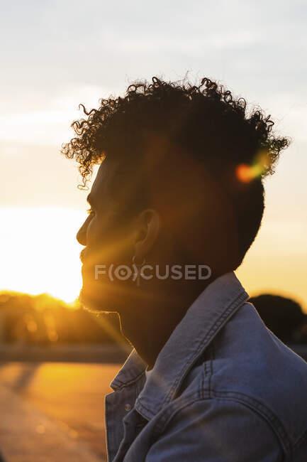 Close-up do jovem vestindo brinco em forma de cruz contra o céu durante o pôr do sol — Fotografia de Stock