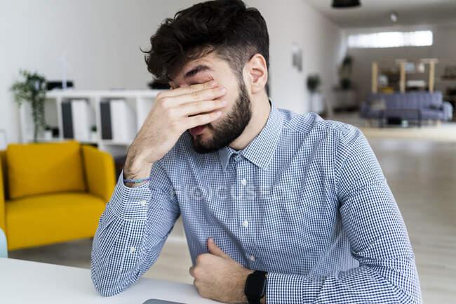 Hombre de negocios cansado sentado en la oficina - foto de stock