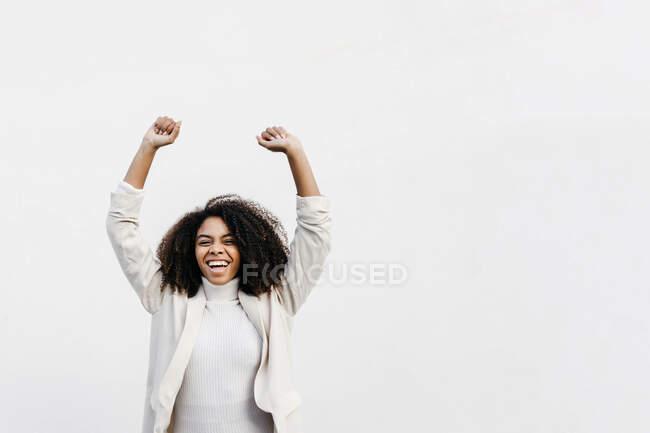 Mujer afro alegre con los brazos levantados gritando mientras está de pie contra la pared blanca - foto de stock