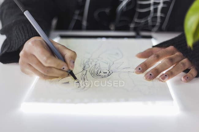 Female design professional drawing on paper at studio — Stock Photo