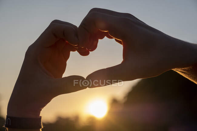 Man making heart shape with hands against sky during sunset — Stock Photo