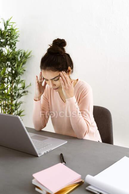 Mujer joven con la cabeza en las manos sentado por ordenador portátil en la mesa en la oficina en casa - foto de stock
