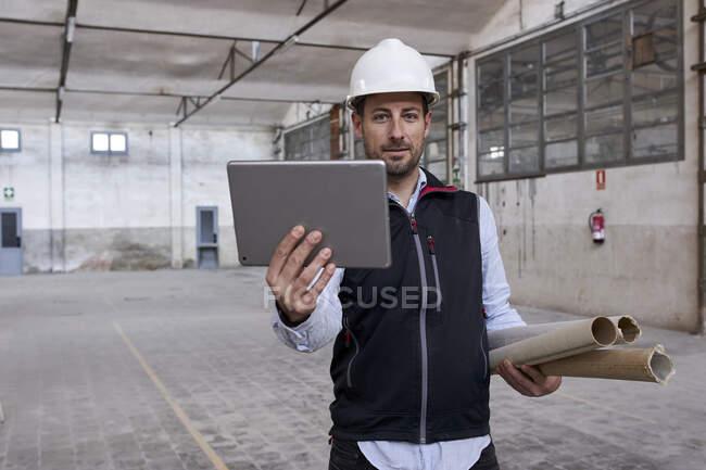 Ingénieur masculin utilisant une tablette numérique tout en travaillant dans la construction sur le site de construction — Photo de stock