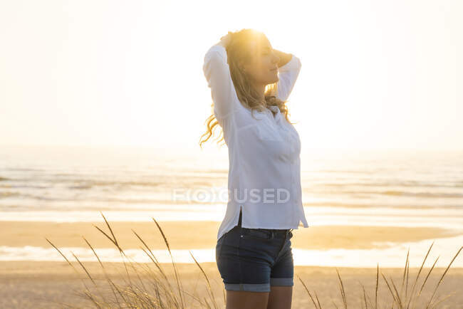 Carefree woman with hands behind head standing at beach — Stock Photo
