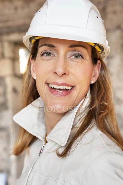 Empreendedora mulher vestindo chapéu duro sorrindo enquanto estava de pé no local de construção — Fotografia de Stock