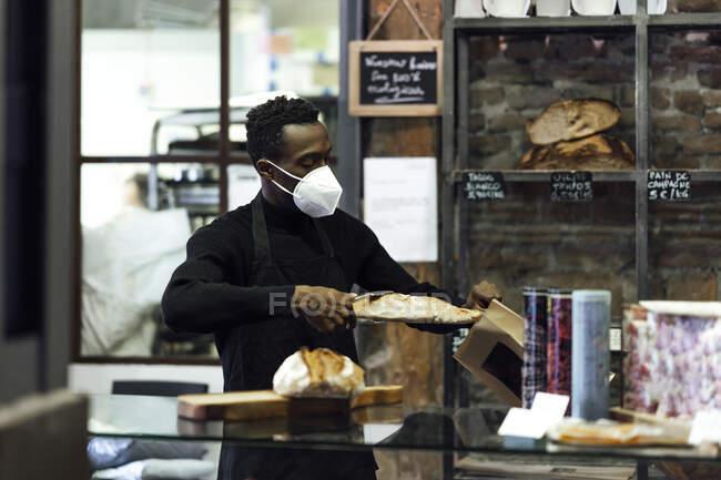 Чоловік, власник пекарні, пакує хліб у паперовій сумці, стоячи біля пекарні. — стокове фото