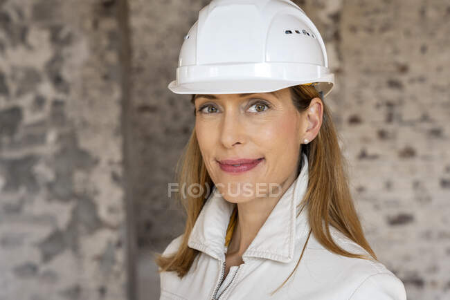 Businesswoman wearing hardhat smiling while standing at construction site — Stock Photo