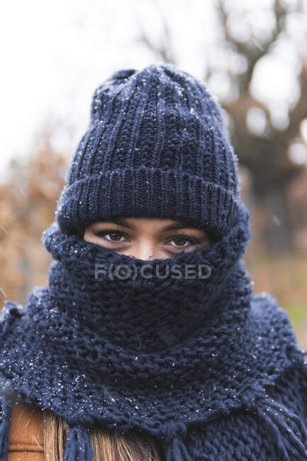Young woman in knit hat and scarf outdoors — Stock Photo