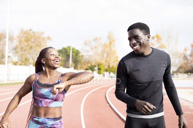 Deportista alegre dando codo golpe al deportista mientras camina en la pista durante el día soleado - foto de stock