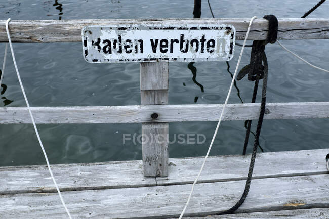 Germany, Schleswig Holstein, Wendtorf, Jetty on Baltic Sea with sign saying bathing prohibited — Stock Photo
