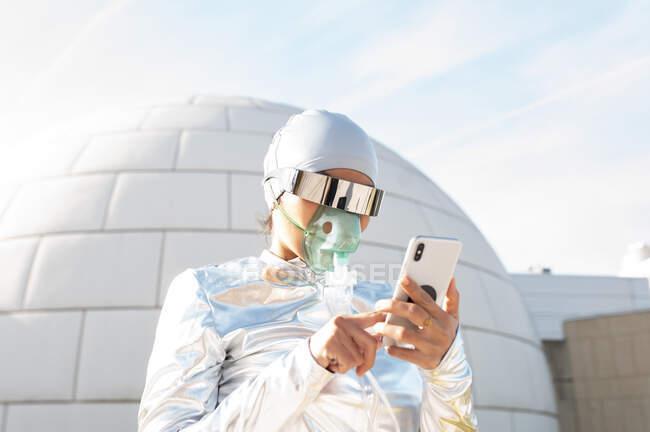 Mujer con traje protector y máscara de oxígeno usando teléfono móvil mientras está de pie contra iglú - foto de stock
