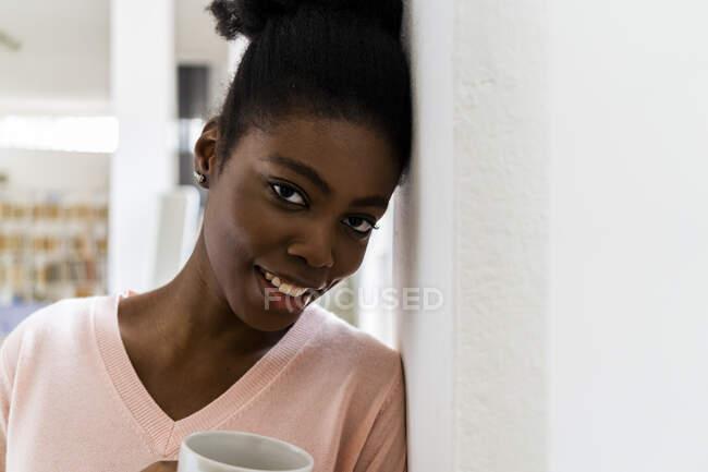 Усміхнена жінка з чашкою кави дивиться, коли нахиляється в стіні вдома. — стокове фото