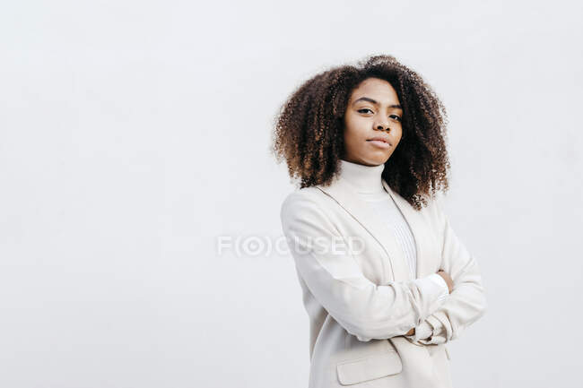 Confident young woman with arms crossed standing against white wall — Stock Photo