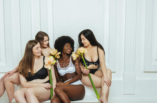 Smiling multi-ethnic group of models in lingerie with flowers looking at each other against white wall — Stock Photo