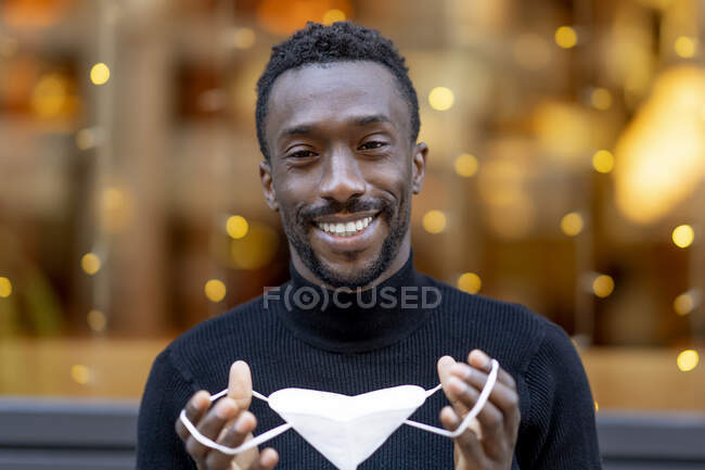 Smiling man holding protective face mask while standing outdoors — Stock Photo