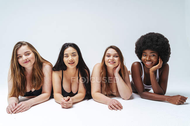 Young women wearing lingerie smiling while lying down in studio — Stock Photo