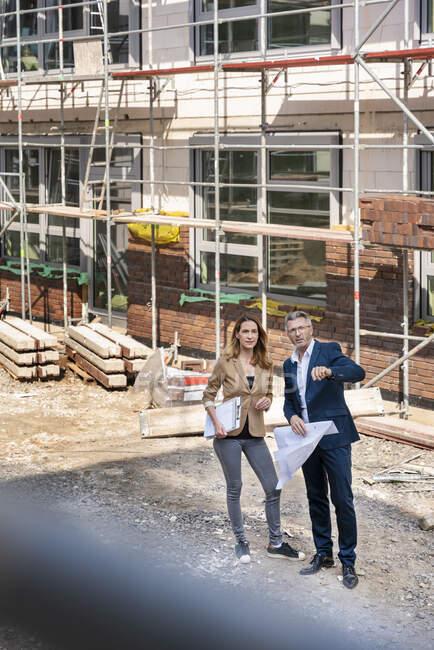 Uomo d'affari avendo discussione con il collega bianco in piedi in cantiere — Foto stock