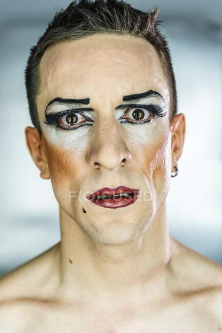 Крупный план портрета трансвестита с макияжем на сером фоне — стоковое фото