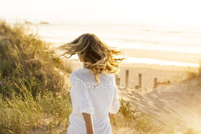 Жінка біжить на пляжі під час заходу сонця. — стокове фото