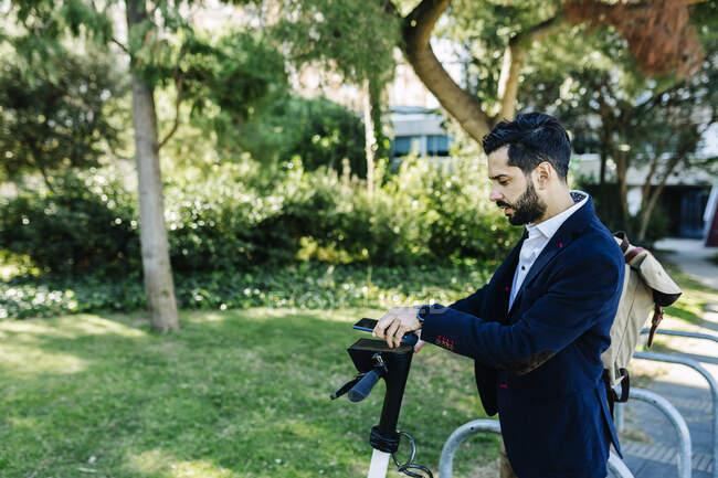 Бізнесмен за допомогою мобільного телефону стоїть на велосипедній станції. — стокове фото