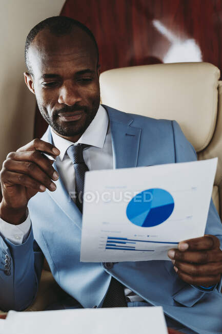 Young businessman examining graph while sitting in private jet — Stock Photo
